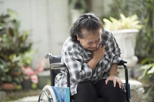 äldre kvinna med hjärtsjukdom som sitter i rullstol foto