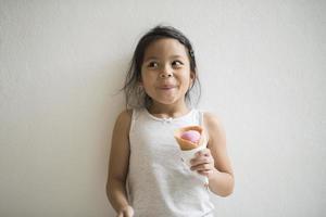 porträtt av en liten flicka som äter glass foto