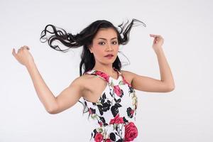 porträtt av en kvinna på vit bakgrund som leker med hår foto