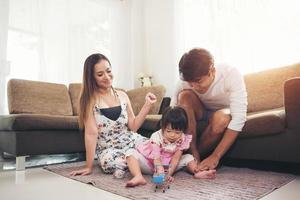 barn med sina föräldrar som leker på golvet hemma foto