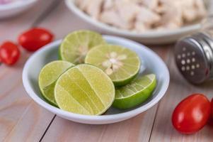 närbild av en skål med skivade limefrukter på ett träbord