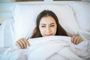 kvinna som vaknar i sin säng, lat på morgonen foto