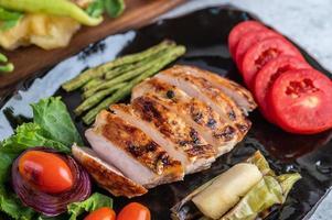 kycklingbiff med salladgrönsaker på en svart platta