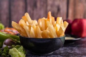 pommes frites i en svart skål foto