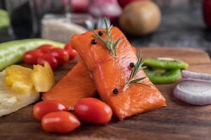 rå laxfiléer med peppar, kiwi, ananas och rosmarin foto