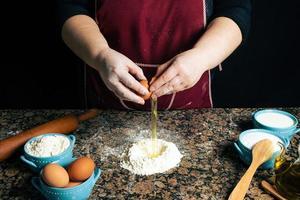 person som bryter ägg i mjöl