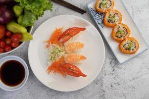 pläterad sushi med sås och ätpinnar foto