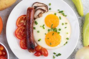 frukost tallrik med stekt ägg, tomater, kinesisk korv och svamp