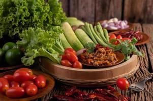 fläsk i en träskål med gurka, långa bönor och sidrätter