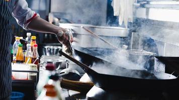 kock som gör en stek i en wok foto