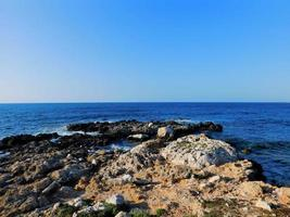 stenig strandpromenad med blått vatten foto