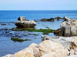 blått vatten nära stenar under dagen foto