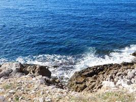 vågor som stänker på en stenig strand foto