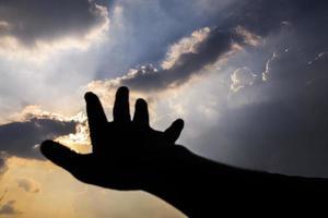 hand som når mot himlen foto