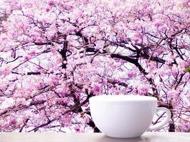 tom vit mugg mockup på träbord. färska trädgrenar med gröna blad suddar bakgrund foto