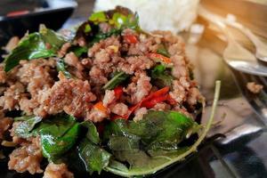 rör stekt hackat kött med chili och basilika och ångat ris på svart tallrik foto