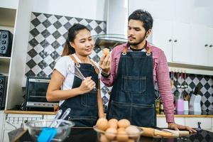 ett lyckligt ungt par som lagar mat hemma