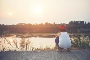 ledsen pojke som sitter vid vattnet foto