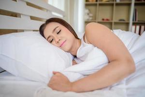 ung kvinna sover i sovrummet och lägger på sängen foto