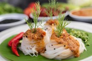 risnudelnudlar toppade med kokosmjölk och grönsaker foto