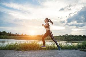 en ung glad kvinnlig löpare som joggar utomhus foto