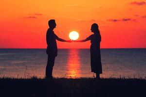 två personer som håller hand vid solnedgången foto