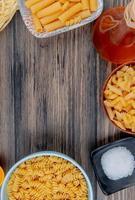 ovanifrån av olika makaroner som ziti rotini tagliatelle och andra med smält smör salt på trä bakgrund med kopia utrymme foto