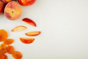 ovanifrån av hela och skivade persikor och gula russin på vänster sida och vit bakgrund med kopieringsutrymme