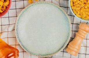 ovanifrån av olika makaroner i skålar salt smör runt plattan på rutigt tyg bakgrund foto