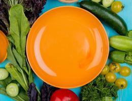 grönsaker som omger en orange tallrik foto