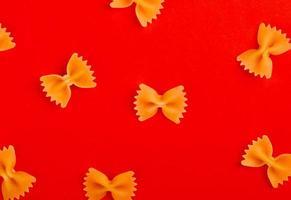 ovanifrån av mönster av farfalle pasta på röd bakgrund