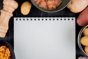ovanifrån av hela riven och stekt potatis runt anteckningsblock med salt på trä bakgrund med kopia utrymme foto