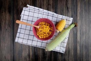 ovanifrån av skål med gul ärta och träsked med snitt och hela liktornar på rutigt tyg och träbakgrund