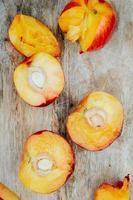 ovanifrån av klippta persikor på träbakgrund foto