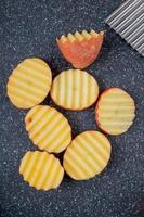 ovanifrån av rufsade potatisskivor på skärbräda som bakgrund foto