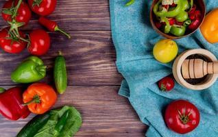 ovanifrån av grönsaker som peppar tomat med vitlök kross och citron på blå tyg och gurka tomat peppar lämnar på trä bakgrund