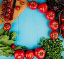 ovanifrån av grönsaker som koriander med spenat basilika tomat med kniv på skärbräda på blå bakgrund med kopia utrymme foto