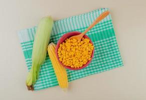 ovanifrån av skål med majsfrön med sked och majskolvar på tyg och vit bakgrund