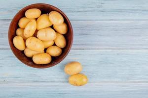 ovanifrån av nya potatisar i skål och på träbakgrund med kopieringsutrymme