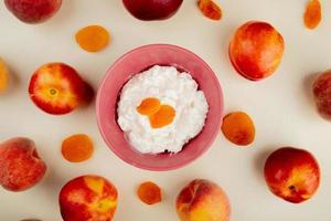 ovanifrån av skål med keso med russin och persikor runt på vit bakgrund