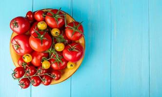 ovanifrån av tomater i skål på vänster sida och blå bakgrund med kopieringsutrymme