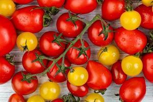 ovanifrån av mönstret av gula och röda tomater på träbakgrund
