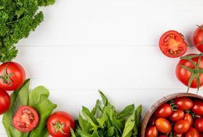 ovanifrån av grönsaker som koriander tomat spenat gröna mynta blad på trä bakgrund med kopia utrymme foto