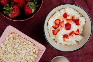 ovanifrån av skål med keso med jordgubbar och skål med havre på bordo bakgrund foto