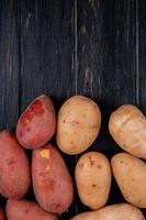 ovanifrån av vita och röda potatisar på träbakgrund med kopieringsutrymme foto
