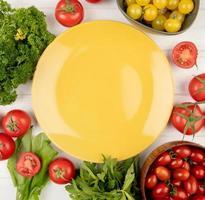 ovanifrån av grönsaker som koriander tomat spenat gröna mynta blad med tom tallrik på mitten på trä bakgrund foto