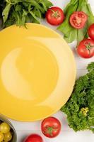ovanifrån av grönsaker som koriander tomat spenat gröna mynta blad med tom tallrik på trä bakgrund foto
