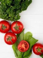 ovanifrån av grönsaker som koriander tomat spenat på trä bakgrund foto