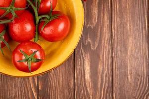 ovanifrån av tomater i skål på vänster sida och träbakgrund med kopieringsutrymme