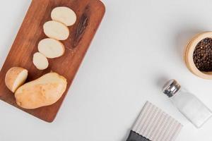 potatis på skärbräda med salt svartpeppar och potatischipskärare på vit bakgrund foto